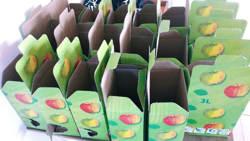 Die leeren Kartons warten auf die abgefüllten Apfelsaft-Beutel