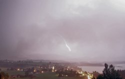 Heftiger Blitzeinschlag während einem Gewitter hinter Hopfen am See bei Nacht.